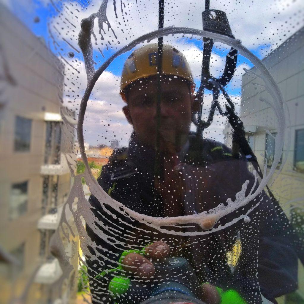 Промышленный альпинист удаляет налет со стекла